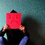 man holding up a sad face